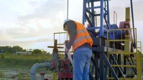 Un homme inspecte la plate-forme pétrolière banque de vidéos