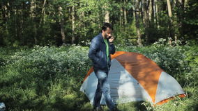 Un homme invitant le téléphone près de la tente Début de la matinée dans la forêt clips vidéos