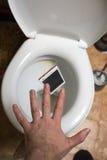 Un homme jette le téléphone dans la toilette photographie stock