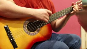 Un homme jouant la guitare acoustique à l'intérieur banque de vidéos