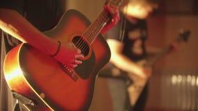 Un homme jouant la guitare acoustique - une représentation avec la bande dans le club banque de vidéos