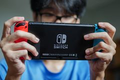 Un homme jouant le commutateur de Nintendo photographie stock