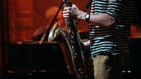 Un homme jouant le saxophone dans une barre de jazz, un autre homme jouant les clés dans le dos clips vidéos