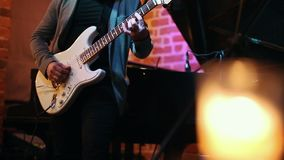 Un homme joue la guitare à une partie dans une barre de jazz, dans le cadre seulement ses mains banque de vidéos