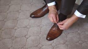 Un homme laçant vers le haut des chaussures clips vidéos