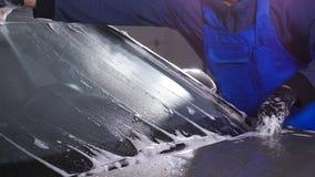 Un homme lave le verre de voiture Concept de station de lavage manuelle banque de vidéos