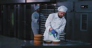 Un homme leurrant avec une barbe utilisant un équipement de cuiseurs finit de décorer l'intérieur du gâteau, alors qu'un gros hom banque de vidéos