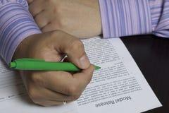 Un homme lit une libération modèle avant de la signer Photographie stock libre de droits