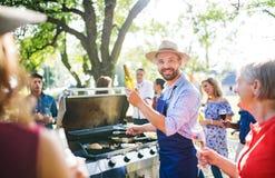 Un homme mûr avec la famille et les amis faisant cuire et servant la nourriture sur une partie de barbecue Images libres de droits