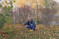 Un homme mûr s'est tapi sur l'herbe avec les feuilles tombées images libres de droits