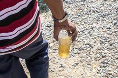 Un homme a marché dans la main avec de la bière photo stock