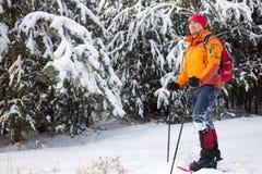 Un homme marchant dans la neige avec un sac à dos Photos libres de droits