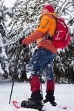 Un homme marchant dans la neige avec un sac à dos Images libres de droits