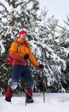 Un homme marchant dans la neige avec un sac à dos Image libre de droits