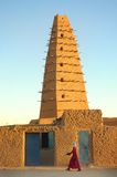 Un homme marchant devant la mosquée d'Agadez photo stock