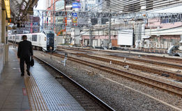 Un homme marchant loin à la plate-forme de train Photographie stock libre de droits