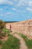Un homme marchant près d'un mur en pierre dans la zone protégée du plateau de Homhil, île de Socotra, Yémen Photographie stock