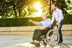 Un homme marche en parc avec son père, qui s'assied dans un fauteuil roulant L'homme et le vieil homme sont heureux Photo libre de droits