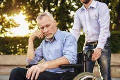Un homme marche en parc avec son père, qui s'assied dans un fauteuil roulant Le vieil homme est triste Photos stock