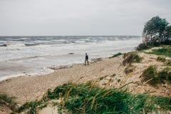 Un homme marche le long de la plage dans une tempête photos stock
