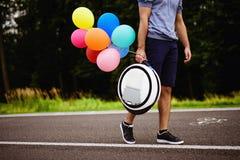 Un homme marche le long du chemin de parc avec un monoclean dans des ses mains À lui sont les boules gonflables multicolores join Photo libre de droits