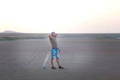 Un homme marche le long du rivage du lac avec le panneau de patin Un rivage de lac salt Salt Lake Photographie stock