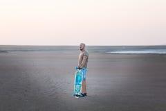 Un homme marche le long du rivage du lac avec le panneau de patin Un rivage de lac salt Salt Lake Photos stock