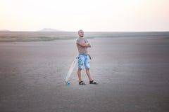 Un homme marche le long du rivage du lac avec le panneau de patin Un rivage de lac salt Salt Lake Photo libre de droits