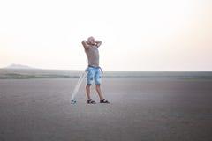 Un homme marche le long du rivage du lac avec le panneau de patin Un rivage de lac salt Salt Lake Images stock