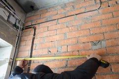 Un homme mesure le câblage, exactitude est important photos stock