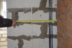 Un homme mesure le câblage, exactitude est important photographie stock libre de droits