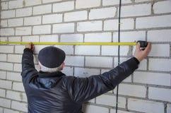 Un homme mesure le câblage, exactitude est important images libres de droits