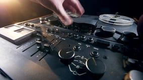 Un homme met des bobines avec la bande sur un enregistreur et pousse un bouton banque de vidéos