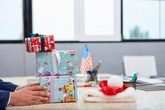 Un homme met quelques boîte-cadeau sur le bureau Dans le bureau Photos stock