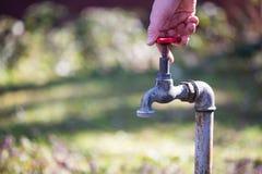 Un homme mettant en marche un robinet Photo libre de droits