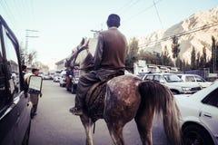 Un homme montant un cheval le long de la route dans la ville de Skardu photos stock