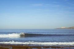Un homme montant les vagues sur le ressac Photos libres de droits