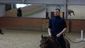 Un homme montant un cheval brun autour de l'arène Race de cheval de Don banque de vidéos