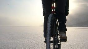 Un homme montant une bicyclette à travers un lac congelé banque de vidéos