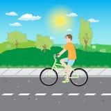Un homme montant une bicyclette sur la route Photo stock