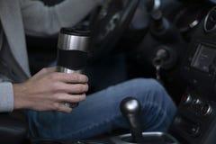 Un homme monte dans une voiture et tient une tasse thermo dans sa main photographie stock libre de droits