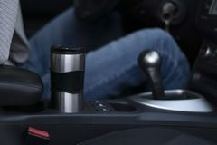 Un homme monte dans une voiture et tient une tasse thermo dans sa main photo libre de droits