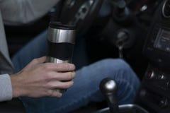 Un homme monte dans une voiture et tient une tasse thermo dans sa main photos libres de droits