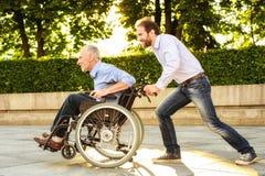 Un homme monte son père dans un fauteuil roulant en parc Ils sont heureux Photo libre de droits