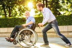 Un homme monte son père dans un fauteuil roulant en parc Ils sont heureux Photographie stock libre de droits