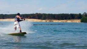 Un homme monte son Wakeboard à un parc de câble, mouvement lent tours de embarquement de sillage clips vidéos