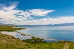 Un homme monte une bicyclette en descendant à un lac magnifique de montagne photos libres de droits