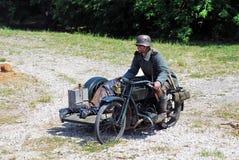 Un homme monte une rétro motocyclette de style Photos stock