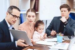 Un homme montre à une femme avec un enfant quelque chose sur le comprimé photo stock