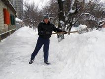 Un homme nettoie la route de la neige Image stock